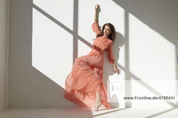 Balletttänzerin in rotem Kleid in Tanzpose an Wand gelehnt