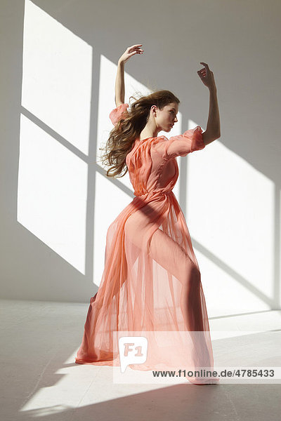 Balletttänzerin in rotem Kleid in Tanzpose