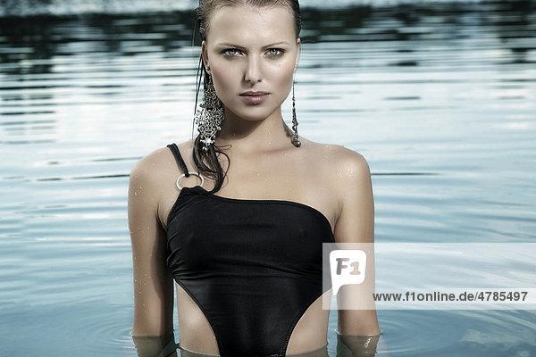 Junge Frau in einem schwarzen Badeanzug und mit nassen Haaren beim Baden in einem See
