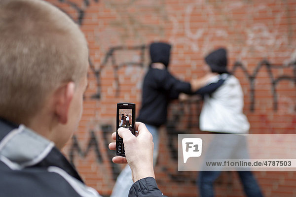 Two boys fighting on the playground while a third films with his cell phone  posed scene