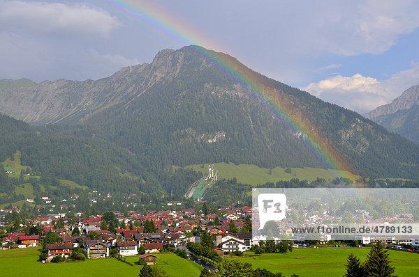 Blick über Oberstdorf mit Regenbogen  dahinter der Schattenberg mit Schattenbergschanze  Oberallgäu  Bayern  Deutschland  Europa