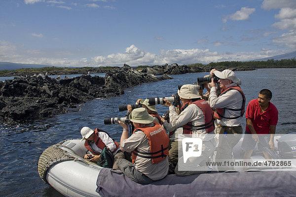 Touristen beim Fotografieren der wild lebenden Tiere von einem Schlauchboot aus  Galapagos-Inseln  Pazifik