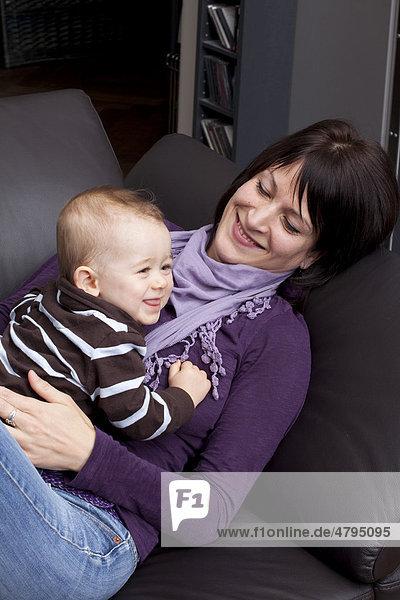 Junge Mutter mit Sohn  8 Monate  gemütlich auf Sofa