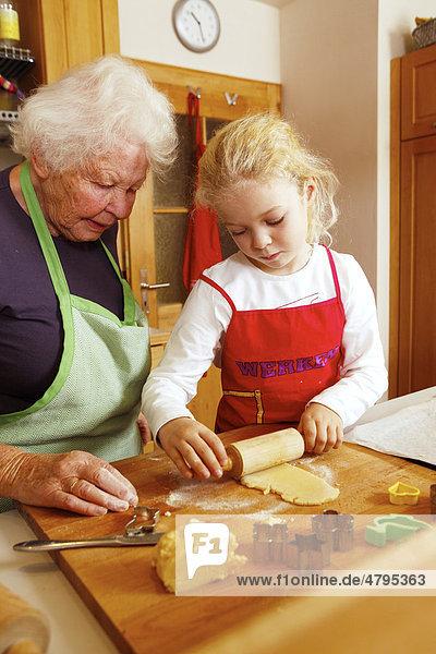 Weihnachtsbäckerei  Oma und Enkelin backen Weihnachtsplätzchen  Mädchen rollt den Teig aus