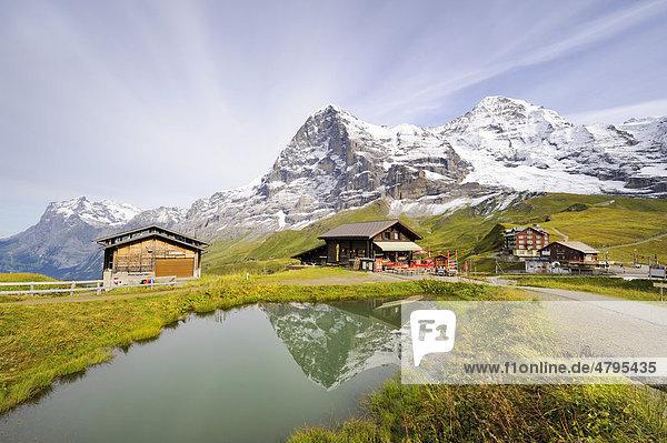 Der Eiger spiegelt sich in einem Bergsee  dahinter ein Bergrestaurant und die Passhöhe Kleine Scheidegg  Kanton Bern  Schweiz  Europa