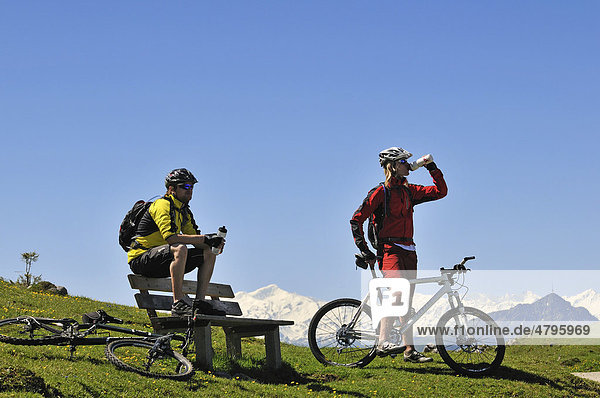 Mountain bikers on Eggenalmkogel  the hills of the alpine pasture in front of the Hohe Tauern Mountains  Reit im Winkl  Bavaria  Germany  Tyrol  Austria  Europe