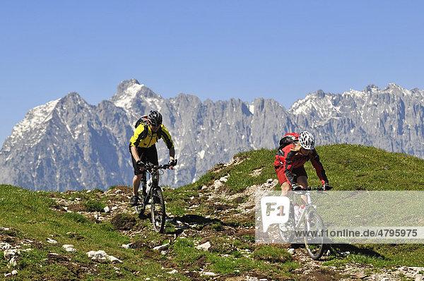 Mountain bikers on the Eggenalm alpine pasture in front of the Wilder Kaiser Mountains  Reit im Winkl  Bavaria  Germany  Tyrol  Austria  Europe