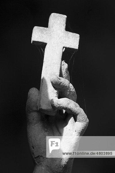 Hand einer Friedhofsfigur hält Kreuz