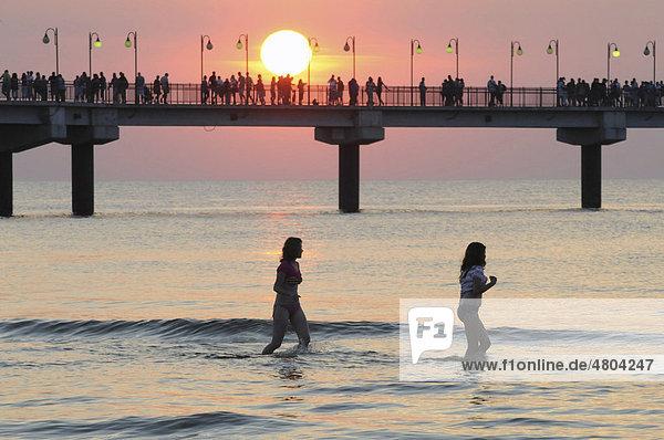 Seebrücke beim Sonnenuntergang mit badenden Mädchen  Miedzyzdroje  Polen  Europa