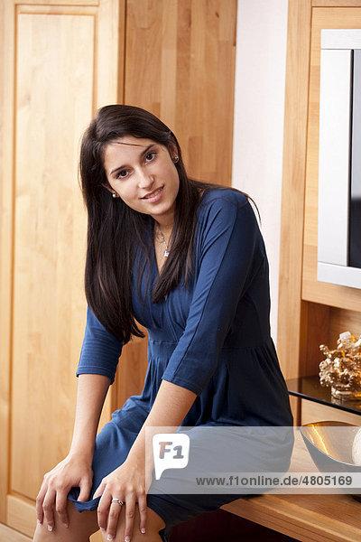 Junge Frau sitzt auf Komode im Schlafzimmer