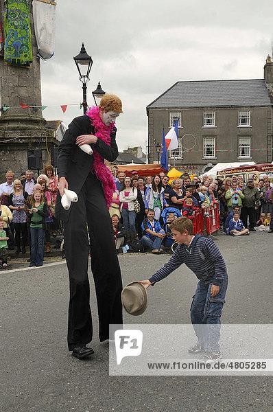 Stelzenmann lässt sich den heruntergefallenen Hut von einem Kind anreichen  bei einem Umzug auf dem Stadtfest von Birr  County Offaly  Midlands  Republik Irland  Europa