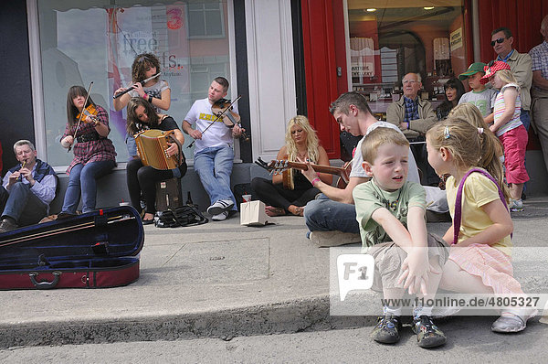 Making music with a violin  an accordion  a guitar and a flute at an Irish music session in the street  music festival Fleadh Cheoil na hEireann in Tullamore  County Offaly  Midlands  Ireland  Europe