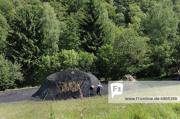 Ein neuer Holzkohlenmeiler wird mit Grassoden abgedeckt und mit Kohlerde abgedichtet  Walpersdorf  Kreis Siegen-Wittgenstein  Nordrhein-Westfalen  Deutschland