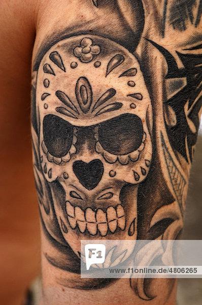Mit einem Totenkopf frisch tätowierter Oberarm eines jungen Mannes