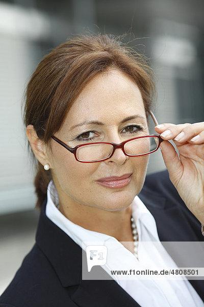 Geschäftsfrau  45 Jahre  im Kostüm  schaut kritisch über den Brillenrand