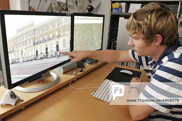 Young man watching city images on Google Street View displayed on a computer screen