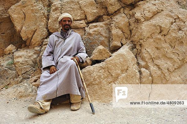 Berber  älterer Mann mit Djellabah und Turban vor einer Felswand  Todra Schlucht  Marokko  Afrika