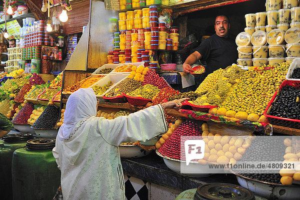 Ältere Frau mit Kopftuch an einem Verkaufsstand im Souk oder Basar  Meknes  Marokko  Afrika