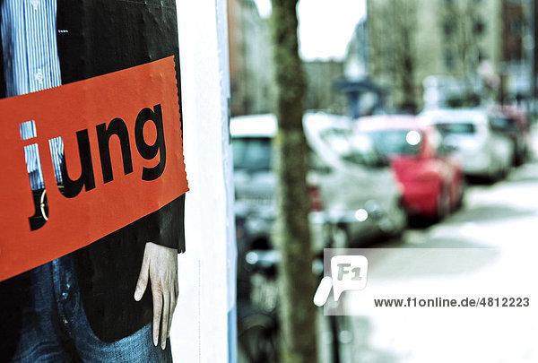 Straßenszene mit Teilansicht einer Plakatsäule  Schriftzug jung