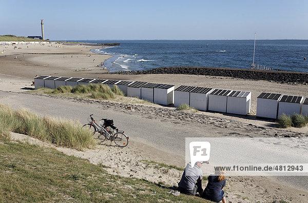 Pärchen mit Fahrrädern macht Rast an einem Strand mit Strandhütten  Westkapelle  Walcheren  Provinz Zeeland  Niederlande  Benelux  Europa