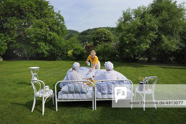 Pensionsgäste mit Zipfelmütze und Schlafhaube frühstücken in den Betten im Garten  Crazy Hotels  Pension Kamerichs  Wittgensteiner Himmelbett  Bad Laasphe  Nordrhein-Westfalen  Deutschland  Europa