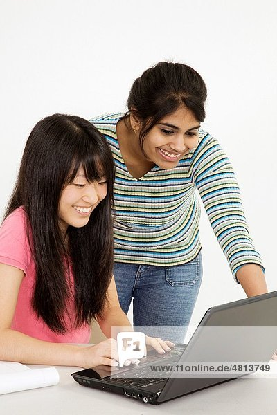 Asian and East Indian teenagers working on a the laptop computer