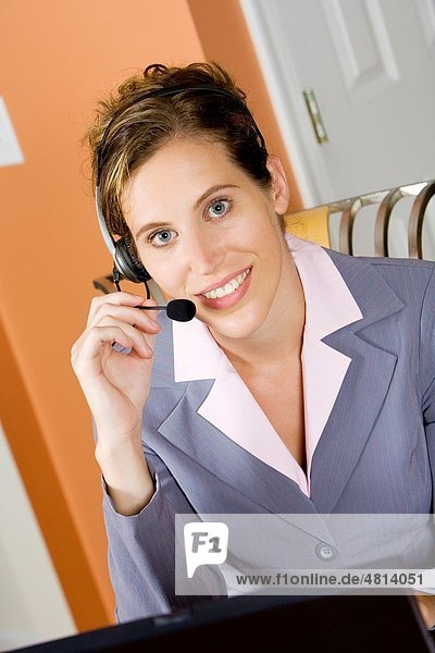 Woman in early 20s working on computer and talking on headset telephone at home