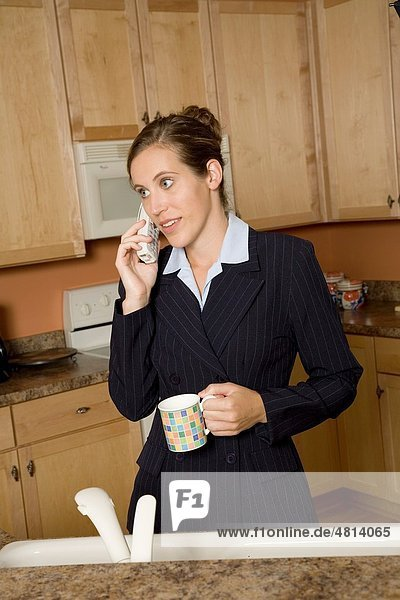 Businesswoman in early 20s standing in the kitchen dresses in a business suit and holding a coffee cup and talking on the telephone