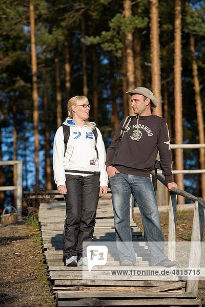 Young Happy Hiking Couple Standing on Wooden Boardwalk Stair in Forest