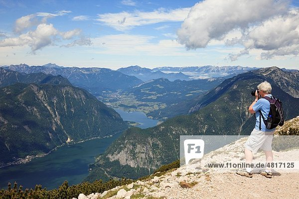 Obertraun  Salzkammergut  Austria  Europe Senior woman photographing the view to Hallstattersee lake from Krippenstein mountain in the Dachstein Massif in the Austrian Alps