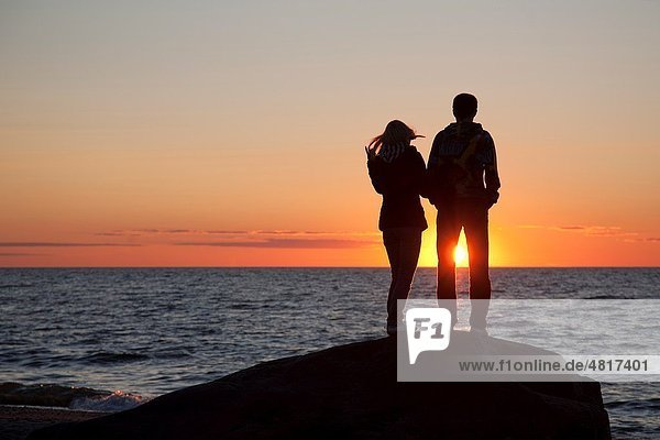 Couple Silhouettes at Sunset on Beach