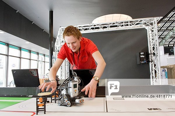 A young student of a technical univesity demonstrates his robots on a large table during a tradefair.