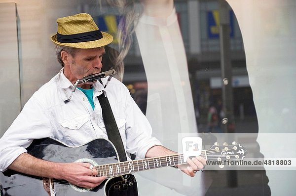 A guitarplayer is making music in front of a shop
