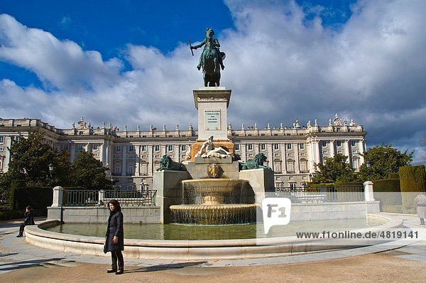 Tourist posing in front of statue of Felipe IV and Palacio Real royal palace Plaza de Oriente square central Madrid Spain Europe