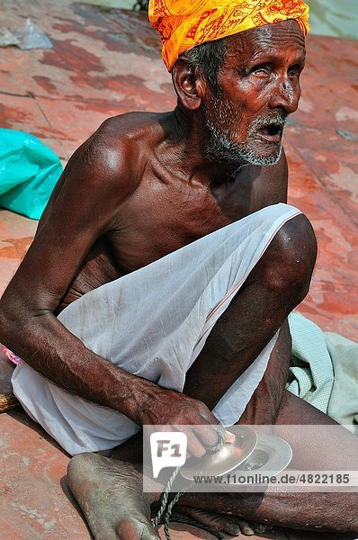 Blind musician singing at Har Ki Pairi ghat by the Ganges river