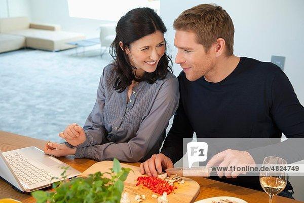 Frau mit Laptop  während der Mann Gemüse hackt