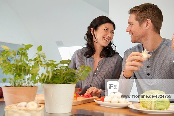 Mann und Frau kochen in der Küche  lächelnd
