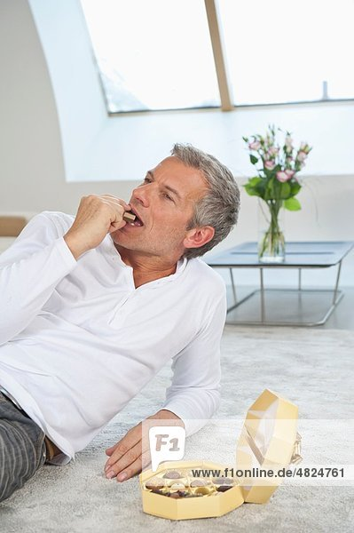 Reifer Mann beim Schokoladenessen zu Hause