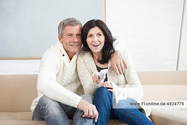 Deutschland  München  Ehepaar mit Fernbedienung auf Sofa