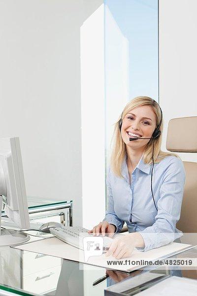 Geschäftsfrau mit Headset und Computer