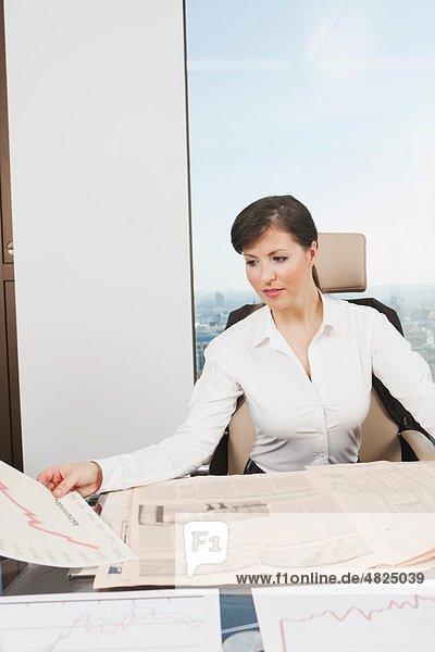 Geschäftsfrau beim Blick auf Grafik und Zeitung