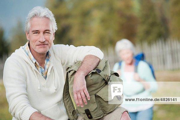 Italien  Südtirol  Reifer Mann lächelt mit Frau im Hintergrund auf Dolomiten