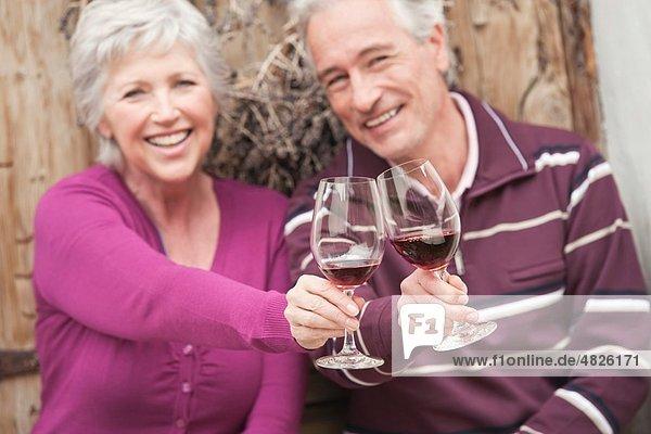 Italien  Südtirol  reifes Paar mit Weinglas auf der Berghütte