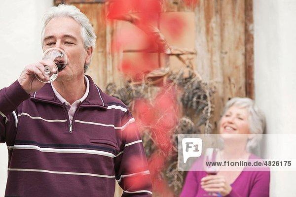 Italien  Südtirol  reifer Mann trinkt Wein mit lächelnder Frau im Hintergrund