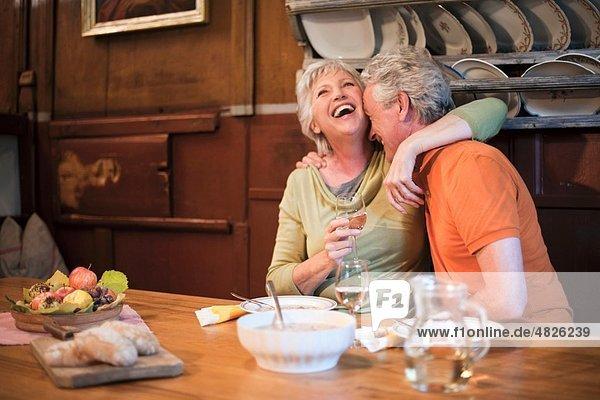 Italien  Südtirol  Reife Paare beim Snacken im Gästehaus  lächelnd