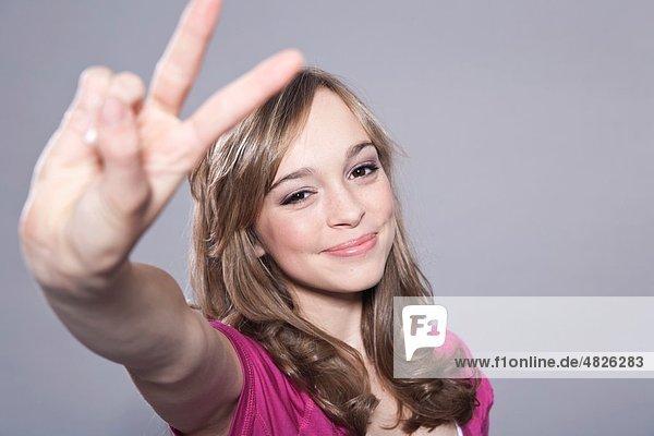 Teenagermädchen mit Friedenssymbol  Portrait Teenagermädchen mit Friedenssymbol, Portrait
