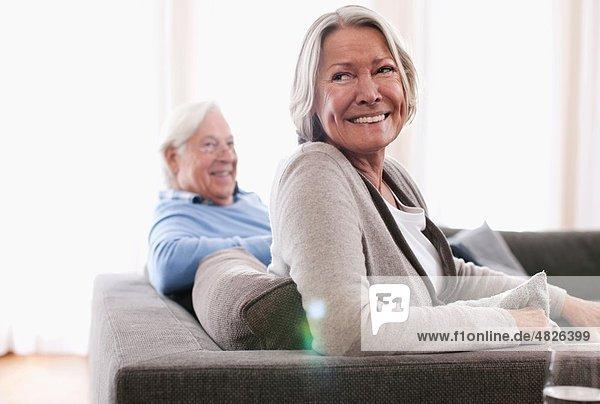 Seniorin lächelt mit Mann im Hintergrund