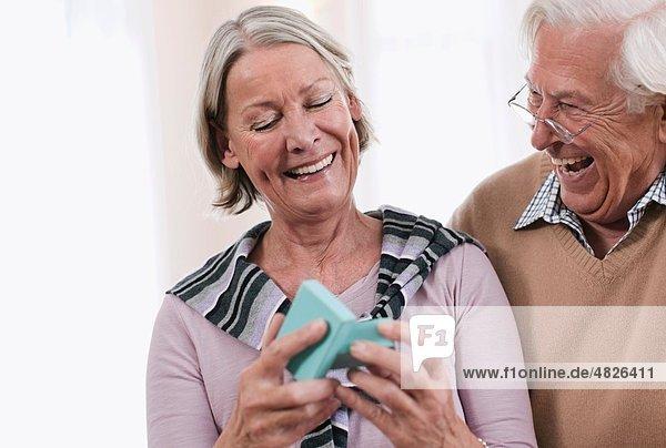 Senior Mann überraschend Frau mit Geschenk  lächelnd