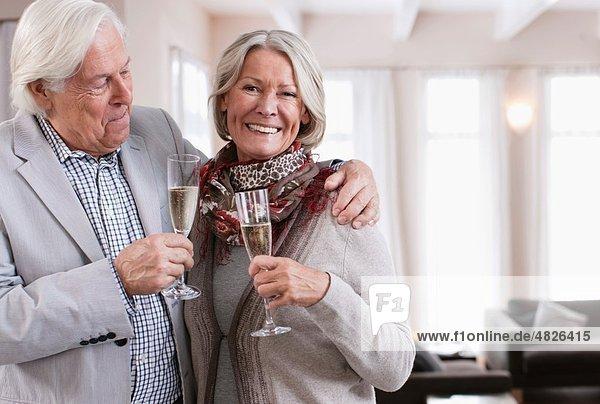 Deutschland  Wakendorf  Seniorenpaar mit Schaumwein  lächelnd