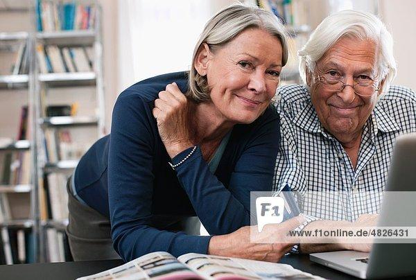 Senior Frau mit Kreditkarte und Mann mit Laptop